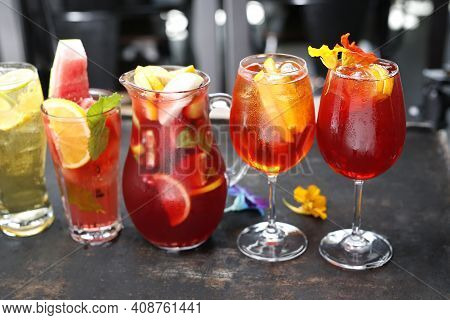 Colorful Lemonades, Drinks, With Ice Cubes, Mint Leaves, Lemon, Orange And Watermelon Slices In Vari