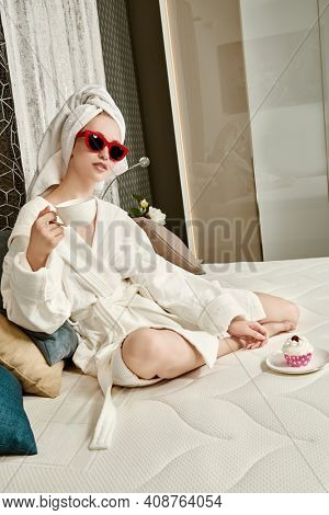 Glamorous young woman in elegant sunglasses, a white bathrobe and with a towel around her hair after a shower lies in her cozy bed, drinks coffee and eats a cake. Luxurious lifestyle.