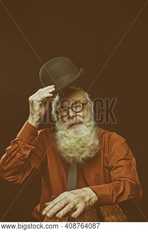 Studio portrait an old-fashioned old man with long gray beard salutes by raising his bowler hat on a black background.