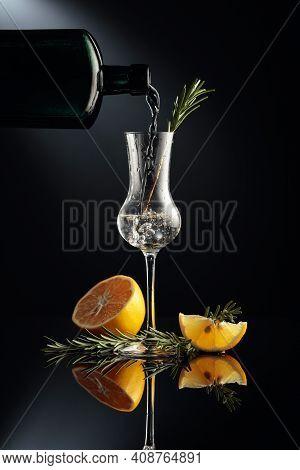 Gin Is Poured In A Small Glass From An Antique Bottle. Gin With Lemon And Rosemary On A Black Reflec
