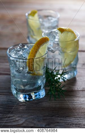Gin With Lemon, Juniper And Ice On A Old Wooden Table. Alcoholic Drink With Lemon Slices And Juniper