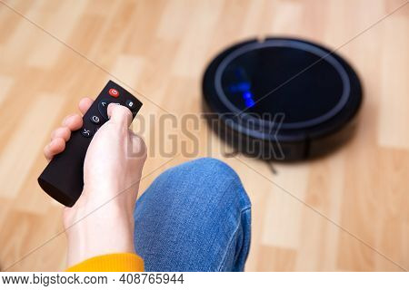 Man Resting While Robotic Vacuum Cleaner Doing Chores, Clean Work At Home. Man Controls A Robot Vacu