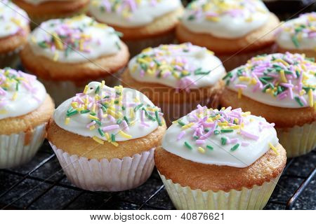 Vanilla Cupcakes decorated With Frosting And Sprinkles