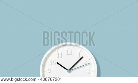 White Plain Analogue Wall Clock On Trendy Pastel Blue Background. Five Past Ten Oclock. Close Up Wit