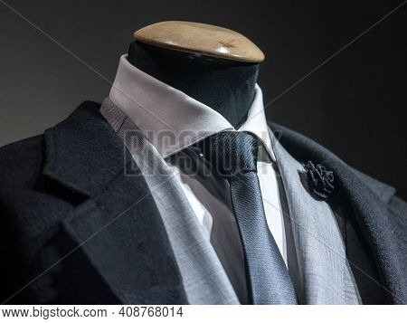 Men Formal Suit, With A White Shirt, A Black Tie, And A Black Lapel Flower Pin And Grey Jacket On Di