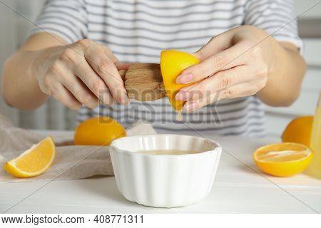 Woman Squeezing Lemon Juice With Wooden Reamer At Table, Closeup