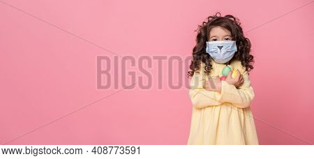 Cute Girl In Protective Mask With Colored Easter Eggs On Pink Background. Covid Easter Concept. Bann