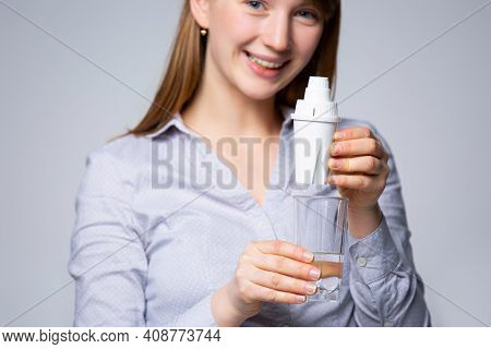 The Womans Hand With A Glass Of Purified Water. The Concept Of Water Purification Through The Minera