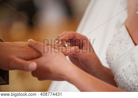 Closeup Of Bride Putting A Wedding Ring Onto The Grooms Finger. Couple Exchanging Wedding Rings. Hig