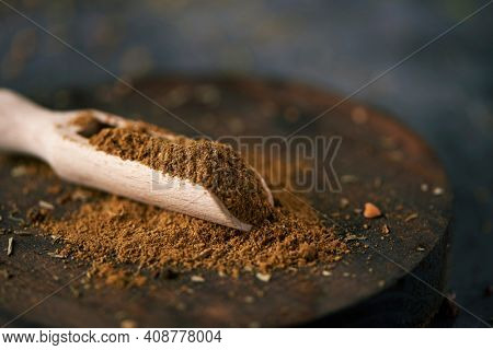 closeup of a wooden measuring scoop full of garam masala, a popular seasoning in the south-asian cuisine, on a wooden tray, placed on dark stone surface