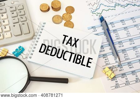 Business Concept - Workspace Office Desk And Notebook Writing Tax Deductible