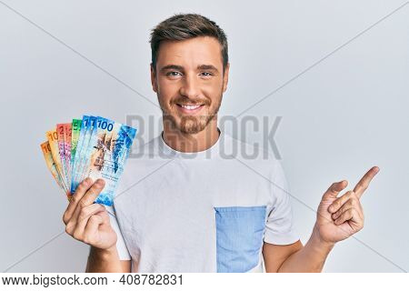 Handsome caucasian man holding swiss franc banknotes smiling happy pointing with hand and finger to the side