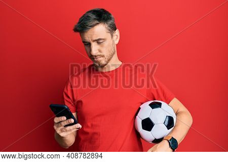Handsome caucasian man holding football ball looking at smartphone relaxed with serious expression on face. simple and natural looking at the camera.