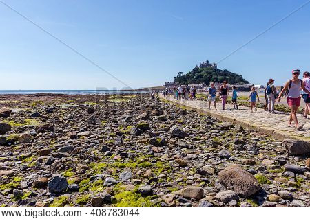 25 July 2018: Marazion, Cornwall, Uk-people Walking On The Causeway Across To St Michaels Mount  In