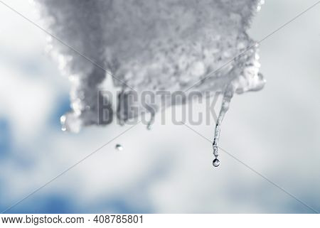 A Droplet Ready To Fall From A Melting Icicle.  Close Up Image Of A Droplet With A Blurry Background