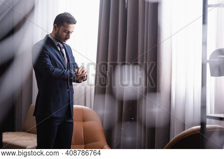Arabian Businessman Looking At Wristwatch In Restaurant.