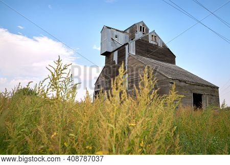 Abandoned Wooden Grain Elevator. An Old, Abandoned, Vintage Wooden Grain Elevator In A Field.