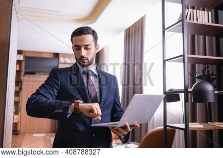 Muslim Businessman Looking At Wristwatch And Holding Laptop In Restaurant.