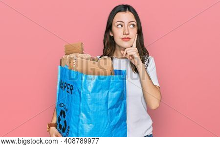Young beautiful woman holding recycling wastebasket with paper and cardboard serious face thinking about question with hand on chin, thoughtful about confusing idea