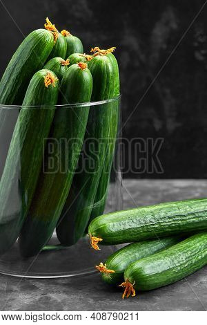 Many Harvest Cucumbers In Vase On The Grey Concrete Background. Top View