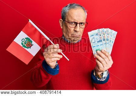 Handsome senior man with grey hair holding peru flag and peruvian sol banknotes skeptic and nervous, frowning upset because of problem. negative person.