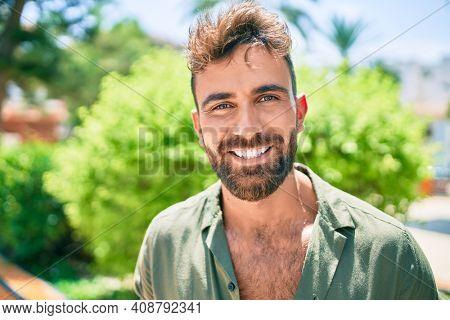 Young hispanic man smiling happy walking at the park