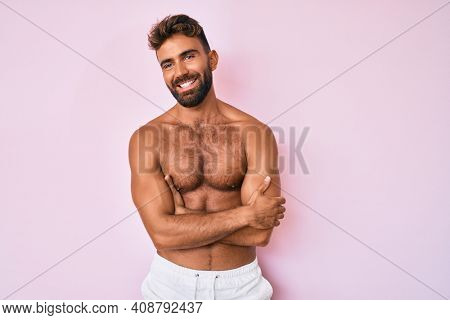 Young hispanic man standing shirtless happy face smiling with crossed arms looking at the camera. positive person.