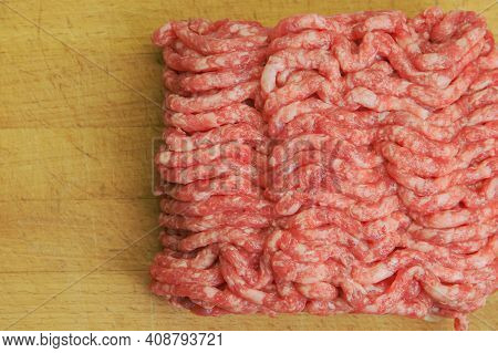 Ground Beef On The Background Of A Worn Kitchen Board Close-up. Empty Space For The Text. Top View