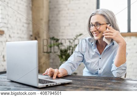 Senior Bossy Businesswoman Has Phone Conversation Working With A Laptop At The Desk In Office. An Ag