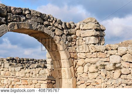 Fragment Of A Dilapidated Antique House Walls With Arch Against The Sky