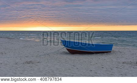 Blue Boat On The Beach At Baltic Sea At Sunset