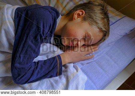 Cute Blonde Boy In Blue Pajama Sleeping And Smiling In Dream In Bed Close-up. Kids Bedroom. Dreaming