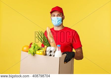 Takeaway Delivery, Covid-19 Quarantine And Groceries Concept. Cheerful Courier In Medical Mask And R