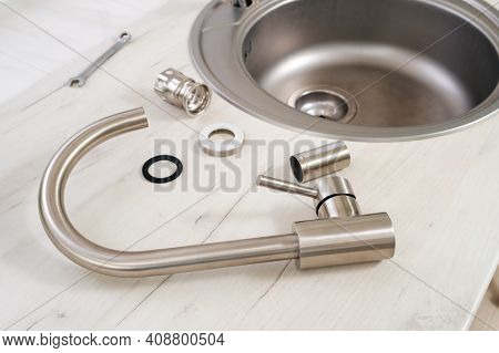 Closeup New Faucet And Tools For Installing Into The Kitchen Sink, Plumbing Work Or Renovation Conce