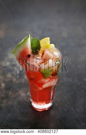 A Glass Full Of Refreshing Drink, Lemonade With Ice Cubes, Mint Leaves, Lemon, Orange, Watermelon Sl