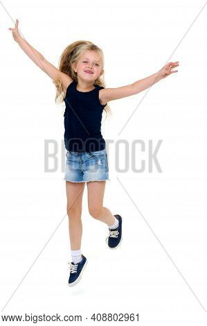 Happy Girl Jumping With Raising Hands. Lovely Girl In Blue Tank Top And Denim Shorts Having Fun Agai