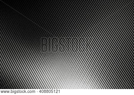 Bended Surface Of Grey Woven Carbon Fibre Composite Sheet. Texture And Pattern Background. Modern Te
