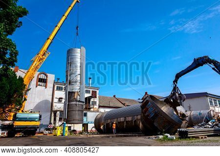 Loader Machine With Hydraulic Grappling Claw And Crane Are Bringing Down Heavy Metal Silo In Industr