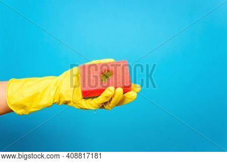 Female Hand In Glove Holding Sponge For Washing With Gel, Blue Background. Home Cleaning, Dishwashin
