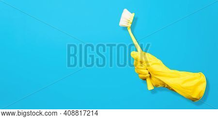Invisible Gloved Hand Holding Cleaning Brush. Blue Background, Copy Space. Levitating Objects. Creat