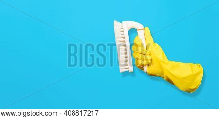 Flying Glove Holding Cleaning Brush. Blue Background, Copy Space. Levitating Objects. Creative Conce