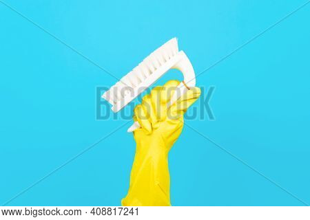 Hand In Yellow Glove Holding Up Brush For Cleaning Surfaces, Blue Background. Equipment For Washing