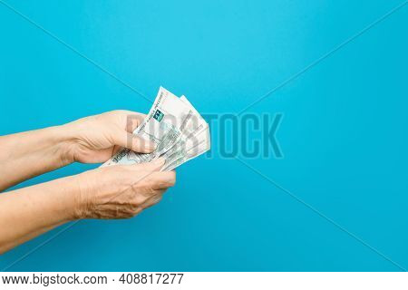 Hands Of An Elderly Woman Counting Rubles On A Blue Background, Copy Space. Pension, Cash Benefit Co