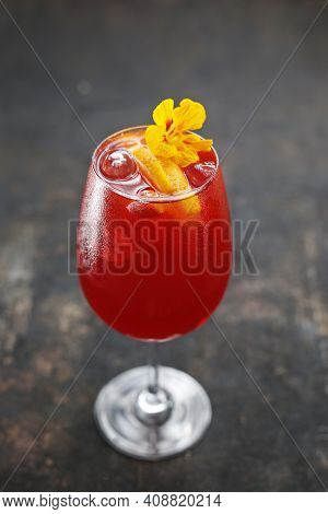 A Top View Of Colourful Lemonade With Ice Cubes And Orange Slices, Decorated With Edible Flower In A