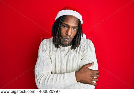 African american man with braids wearing christmas hat shaking and freezing for winter cold with sad and shock expression on face