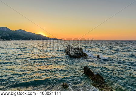 Beautiful Sunset On The Sea. Picturesque Rock In The Sea At Sunset, Kokkari Beach, Samos Island, Gre
