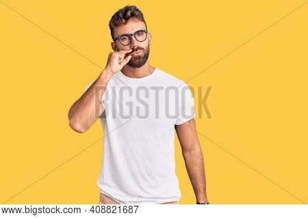 Young hispanic man wearing casual clothes and glasses mouth and lips shut as zip with fingers. secret and silent, taboo talking