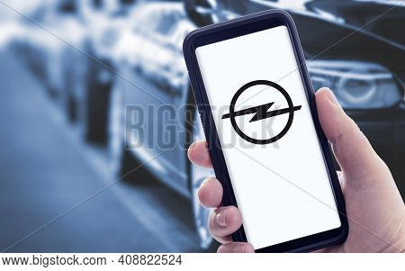 Galicia, Spain; January 09 2021: Hand Holding A Smart Phone With New Opel Logo On Screen And Blurry