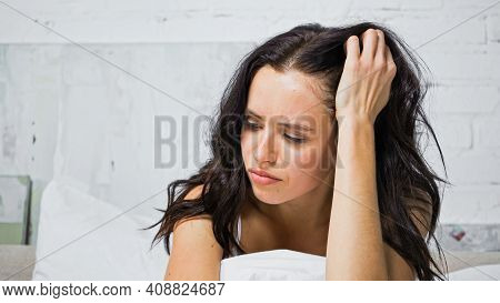 Discouraged Young Woman Touching Head While Sitting In Bedroom.