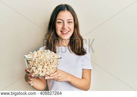 Young brunette woman eating popcorn looking positive and happy standing and smiling with a confident smile showing teeth